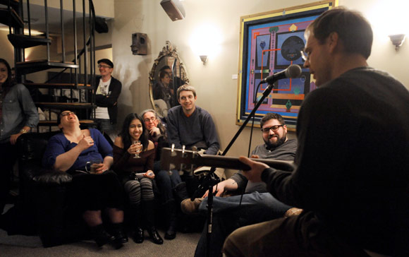 Marck Stanley, right, performs for Seltzer editor-in-chief Pete Cardamone, second from right, and others.