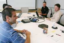Employees sit at a table during a meeting at Merkle